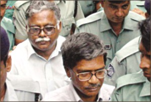 Dr. M. Anwar Hossain (foreground) and Dr. Harun-ur-Rashid in custody