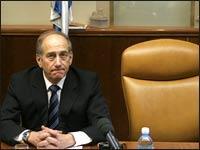 Ehud Olmert sits next to Ariel Sharon's empty chair